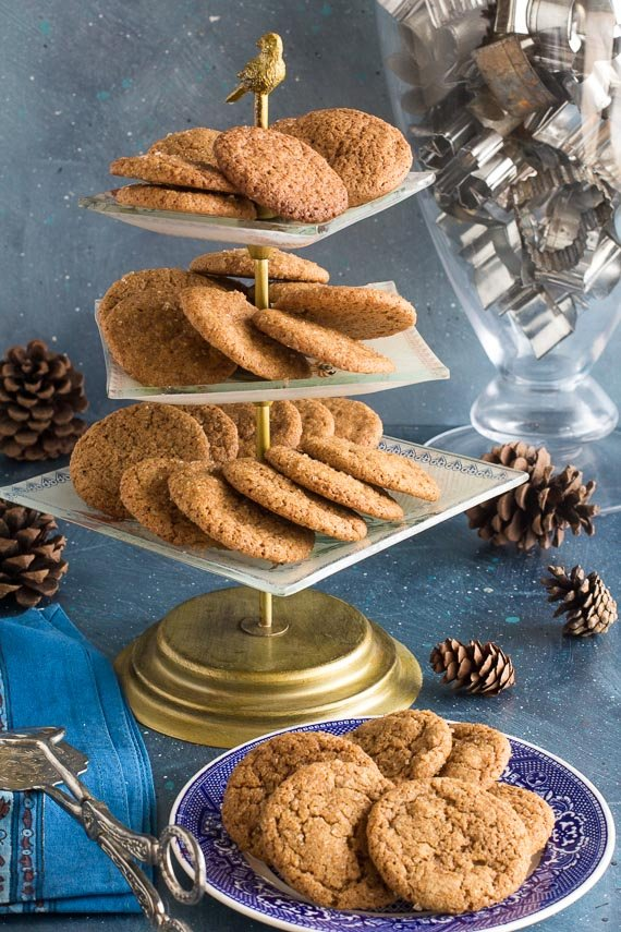 vertical image of low FODMAP gingersnaps on blue plate and tr-level serving dish