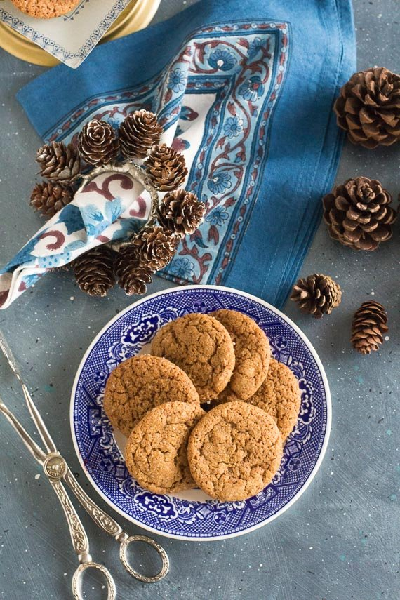 vertical image of low FODMAP gingersnaps with blue napkin and pine cones in background