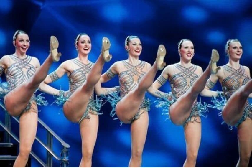Rockette Dancers linked arm in arm kicking their legs up high