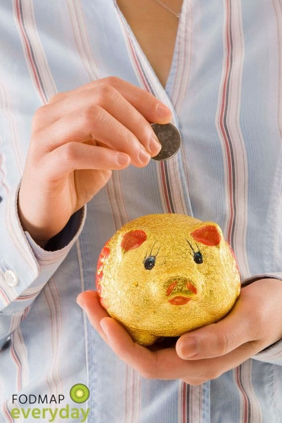 Picture of a woman holding a piggy bank and placing a coin in it.