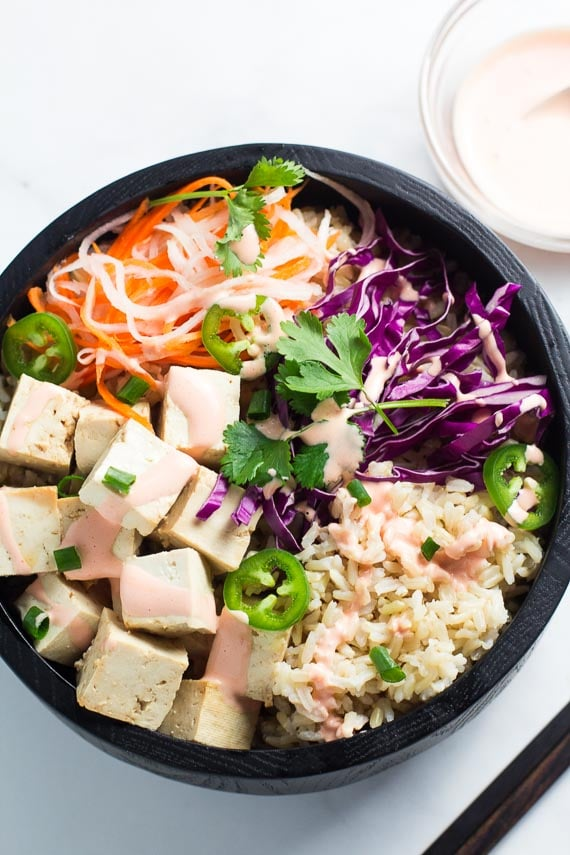 Banh Mi Tofu bowl with brown rice in a dark wooden bowl