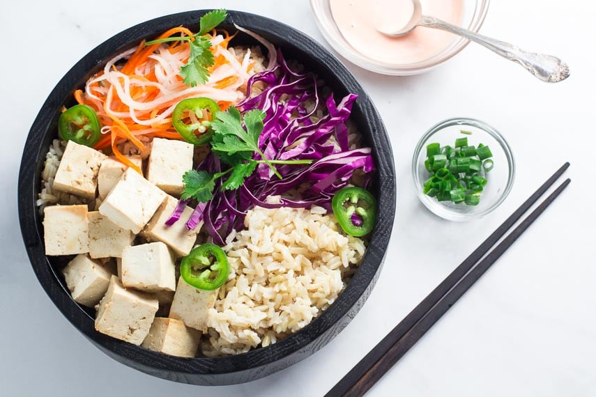Banh mi tofu bowl without sauce in dark bowl; sauce alongside