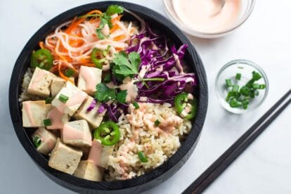 Banh mi tofu brown rice bowl in dark wooden bowl_