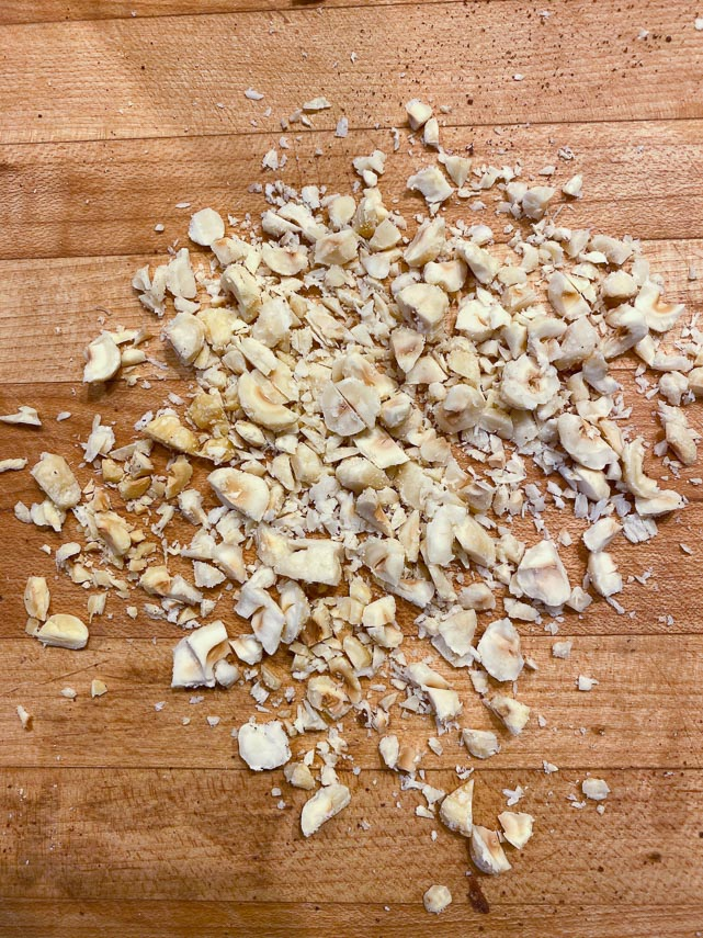 Hazelnuts chopped for biscotti on wooden board