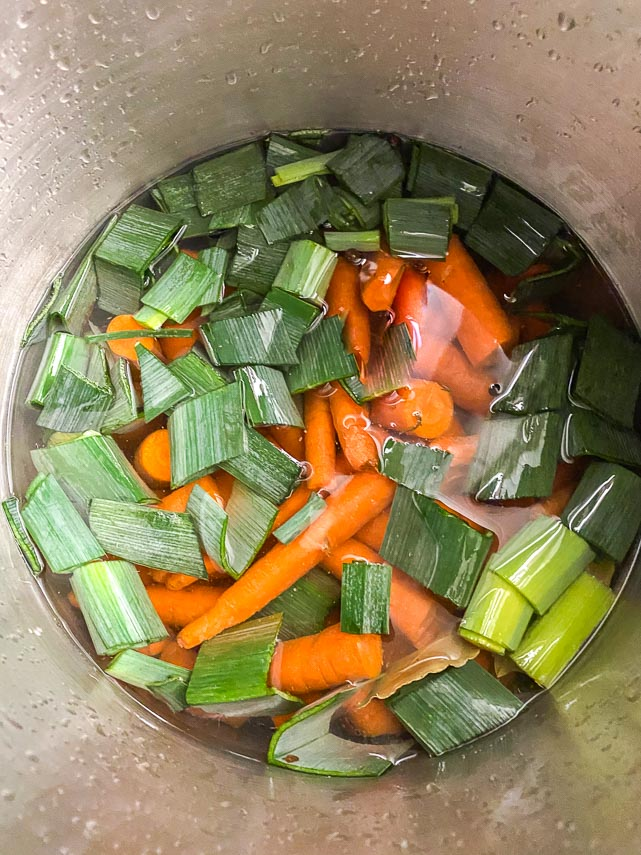 Ingredients for carrot consomme in stockpot about to be simmered