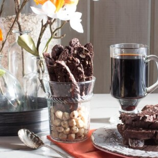 Low FODMAP Chocolate Hazelnut Biscotti stacked on a plate and upright in a glass with flowers and a mug of coffee alongside
