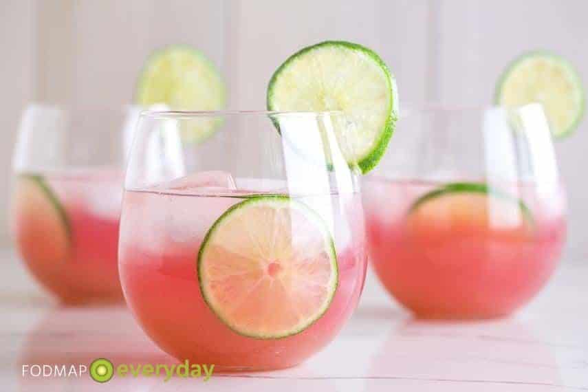 3 glasses of blueberry limeade with slices of lime
