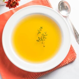 carrot consomme in white bowl with fresh thyme floating on top; orange napkin underneath