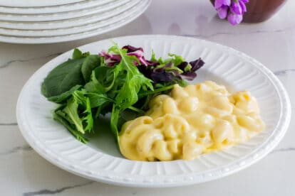 creamy mac and cheese on a white plate with salad on white counter