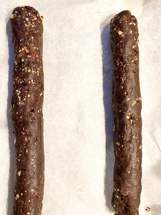 formed logs of chocolate hazelnut biscotti on parchment lined pan, ready for baking