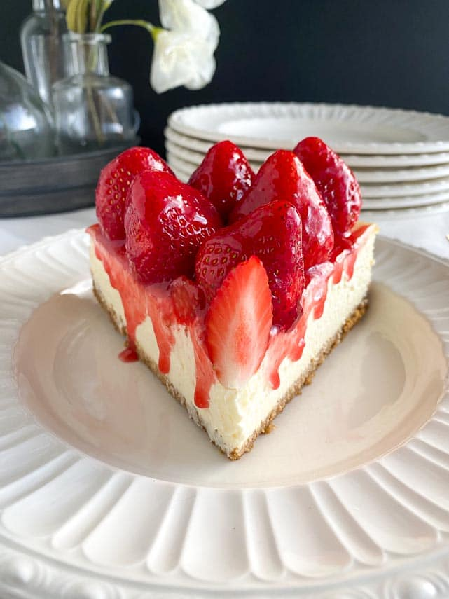 head on image of slice of strawberry glazed cheesecake on white plate