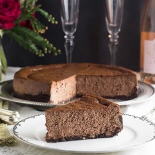 low FODMAP chocolate cheesecake. Whole cake with slcies out in rear; single wedge on white plate up front
