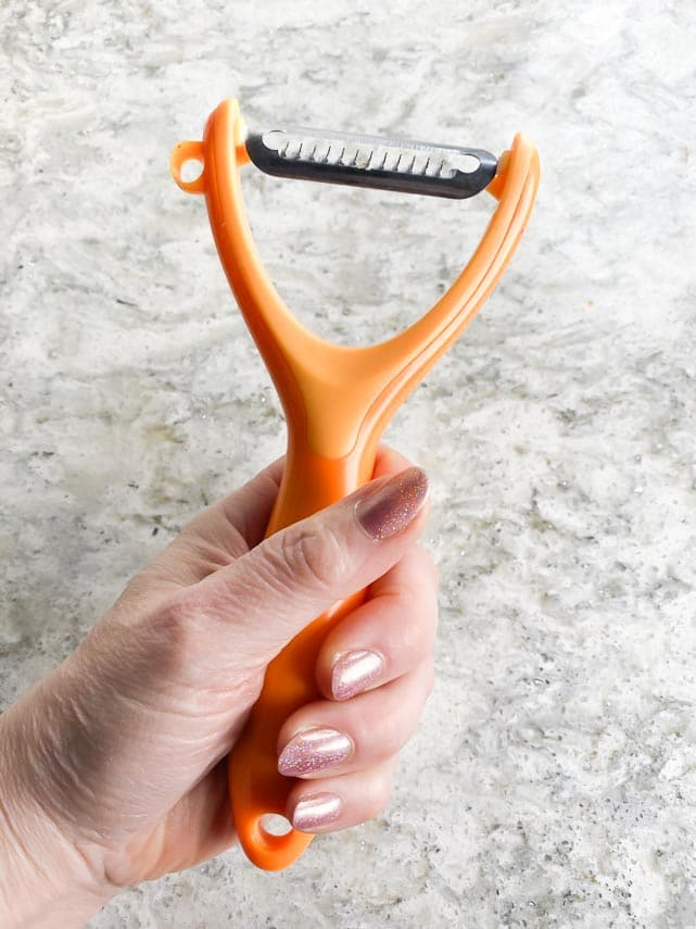 orange colored julienne peeler held in hand