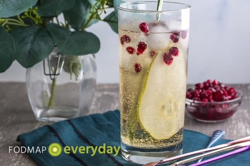low fodmap ginger pomegranate pear sparkler in tall clear glass and stirrer