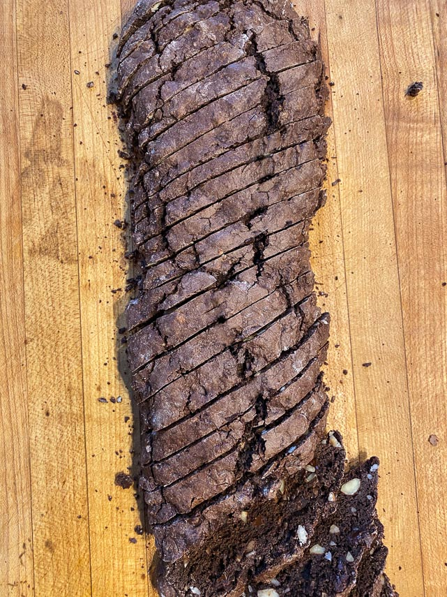 slicing logs of chocolate hazelnut biscotti on wooden board