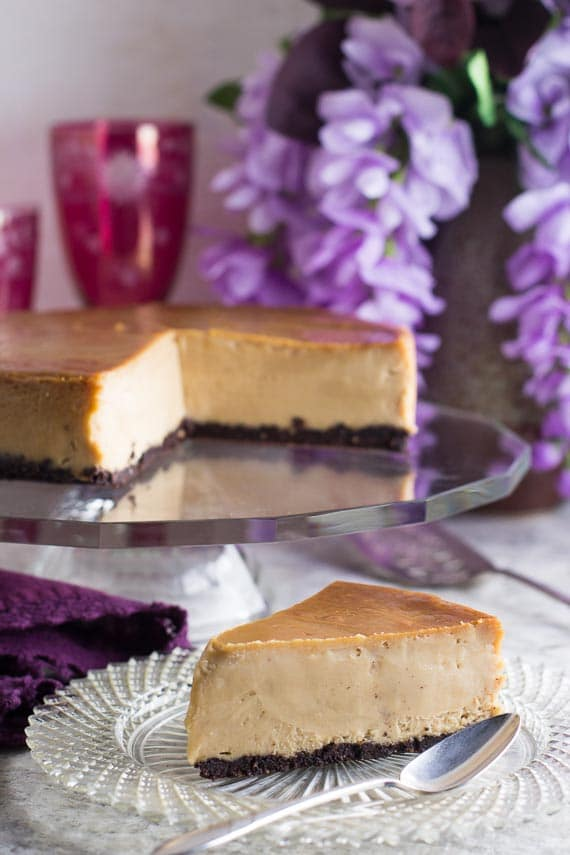 vertical image of frozen low FODMAP peanut butter cheesecake on a cut-glass plate with silver spoon