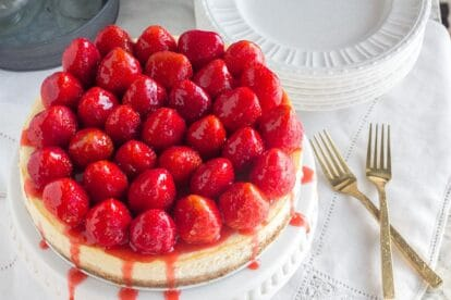 whole strawberry glazed NY style cheesecake on white pedestal with gold forks alongside