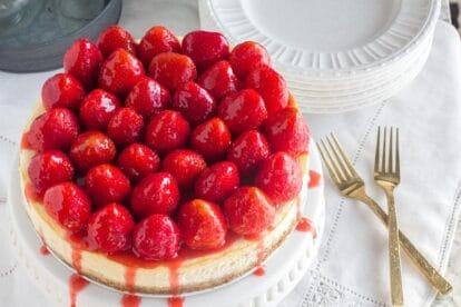 whole strawberry glazed NY style cheesecake on white pedestal with gold forks alongside