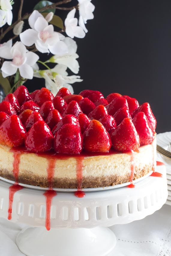 whole strawberry glazed cheesecake on white pedestal; dark background and white flowers in rear