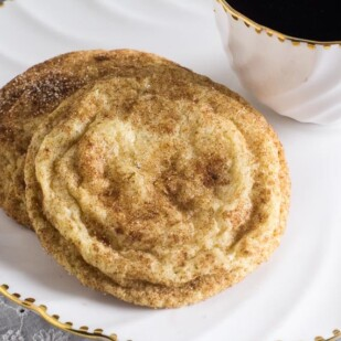 Closeup of Low FODMAP Snickerdoodles on white plate with cup of coffee alongside