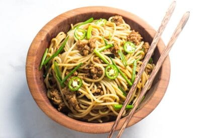 Low FODMAP Pork and Noodles in wooden bowl with chopsticks