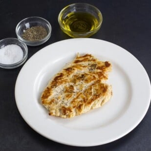 No FODMAP Chicken Paillard on white plate, against dark background