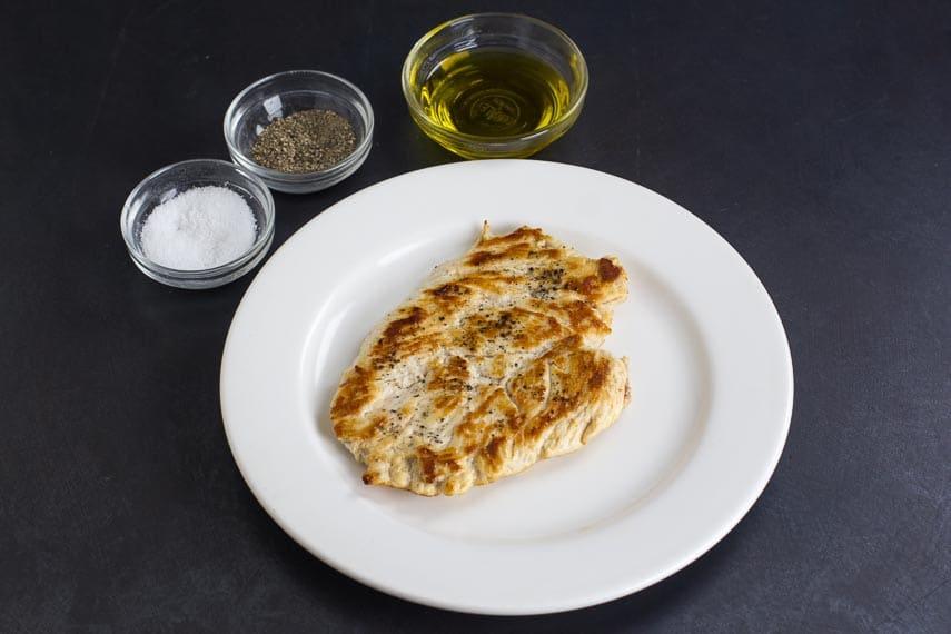 No FODMAP Chicken Paillard on white plate, against dark background