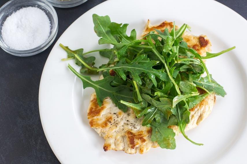 No FODMAP Chicken Paillard on white plate topped with no FODMAP arugula salad