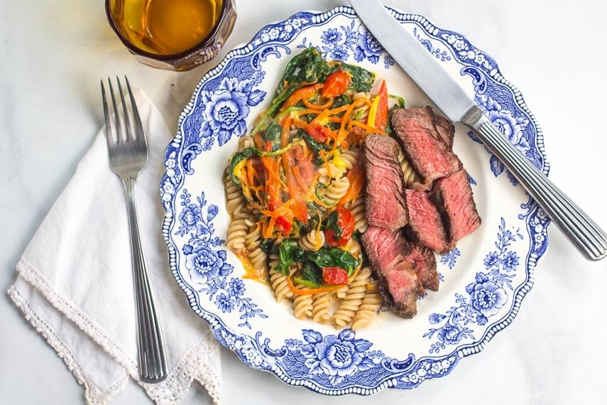 One-Pan Low FODMAP Pasta & Vegetables, steak alongside on blue and white plate