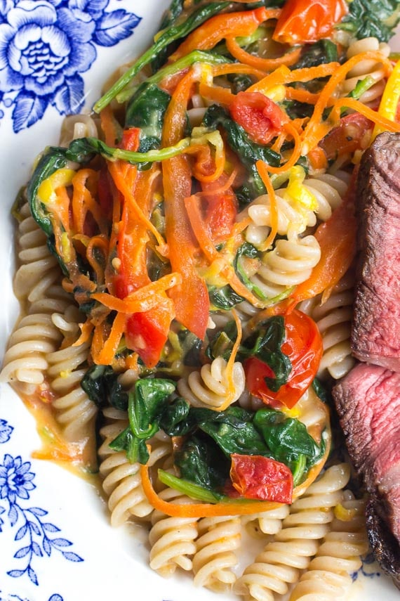 One-pan Low FODMAP Pasta with vegetables on blue and white decorative plate; steak alongside