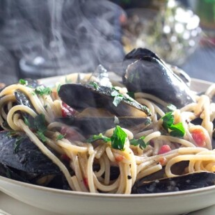 Steaming Low FODMAP Pasta with Mussels in a white bowl