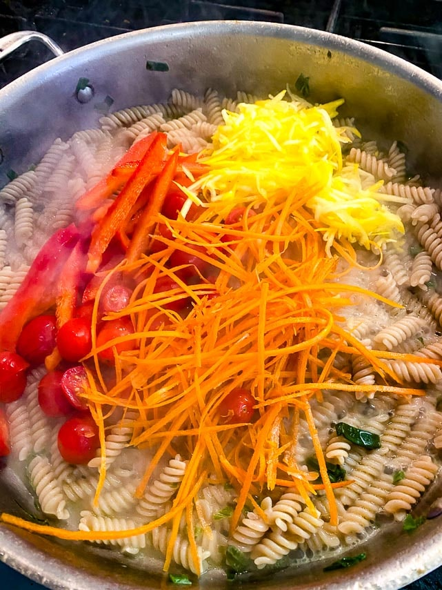 Stir vegetables into pan for one pan low FODMAP pasta & vegetables