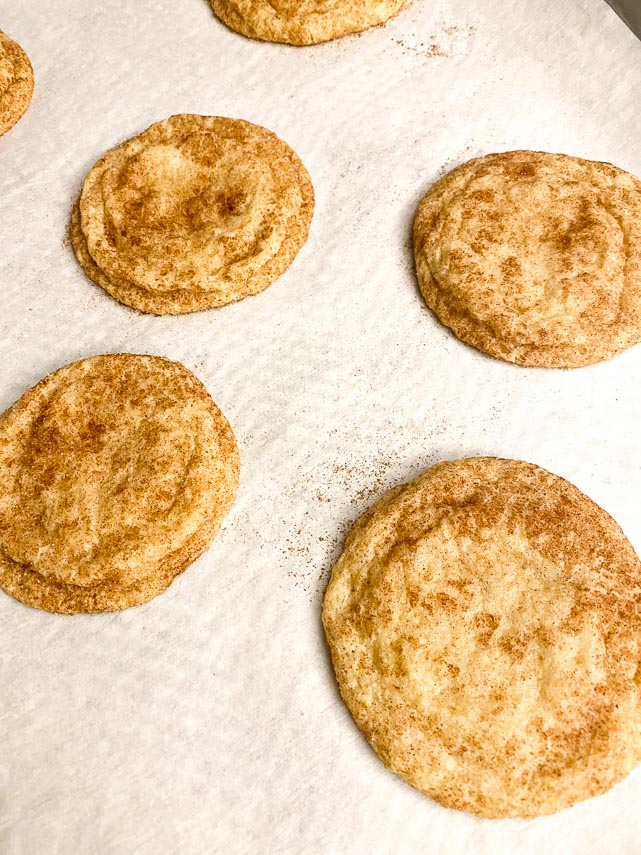 baked low FODMAP Snickerdoodles on parchment lined pan coming out of oven