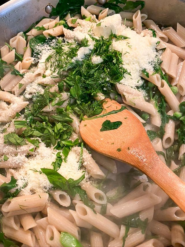 low FODMAP Pasta Primavera cooking; adding butter, cheese and herbs