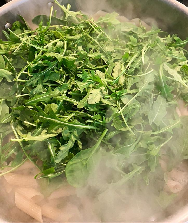 low FODMAP Pasta Primavera cooking; stirring in arugula and spinach