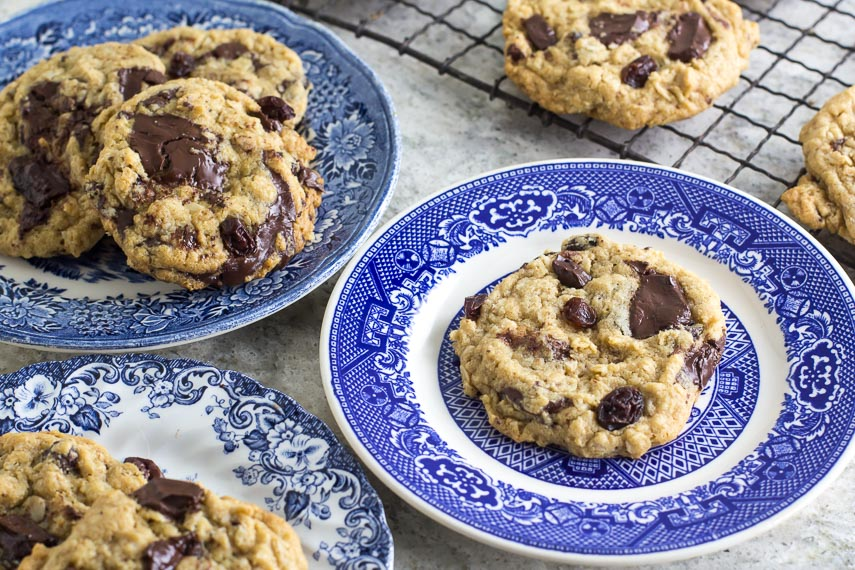 one bowl low FODMAP peanut butter chocolate chunk cookies on blue plates and on rack