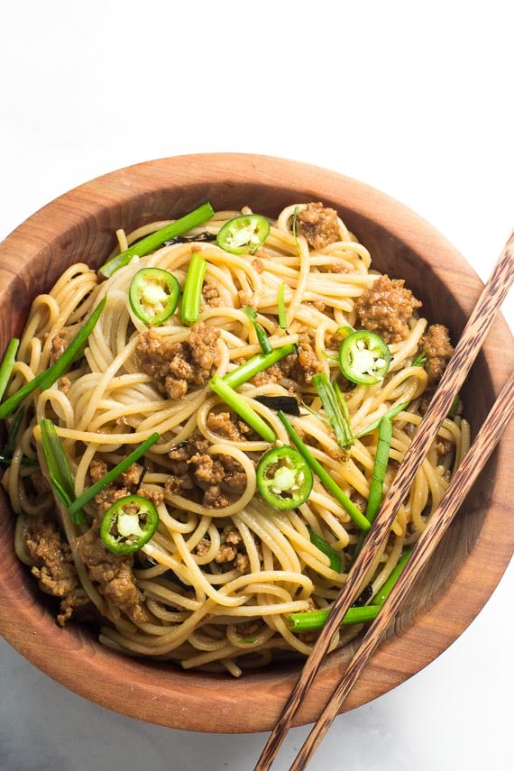 vertical of Low FODMAP Pork and Noodles in wooden bowl with chopsticks