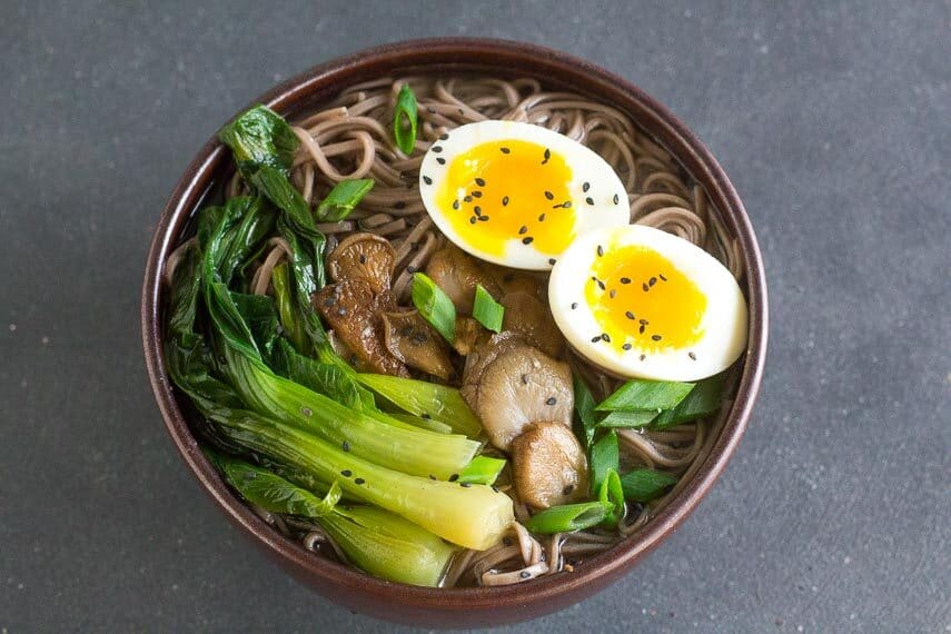 Low FODMAP Soba Miso Soup with Bok Choy and Jammy Eggs in brown ceramic bowl