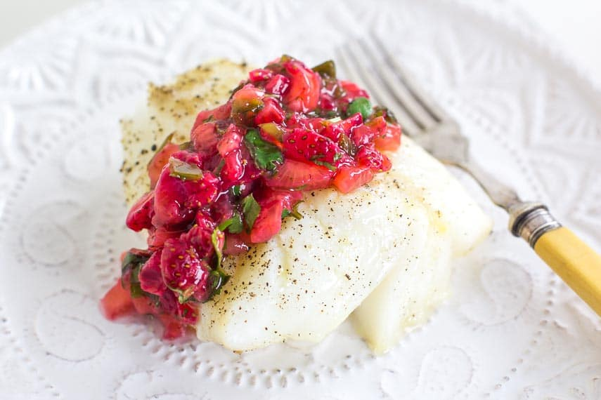 Low FODMAP Strawberry Salsa on cod loin; white plate