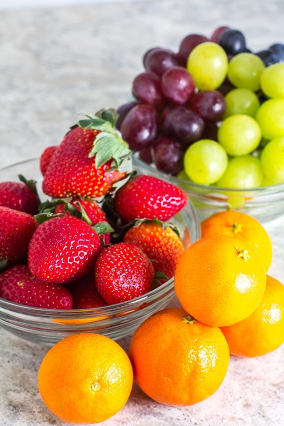 Strawberries, grapes and clementines - all no FODMAP fruits on grey background