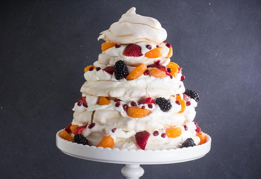 Towering Low FODMAP Fruit Pavlova, horizontal, against dark background