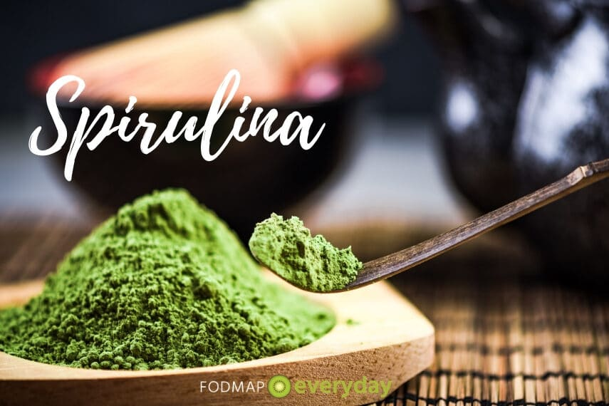 """green spirulina powder with spoonful of it against blurry background with text overlay reading """"spirulina"""""""