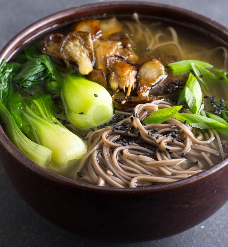 closeup Low FODMAP Soba Miso Soup with Bok Choy in brown ceramic bowl