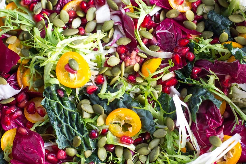 closeup of Low FODMAP Greens with Kumquats and Pomegranate