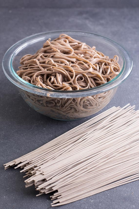 cooked and uncooked soba on dark surface
