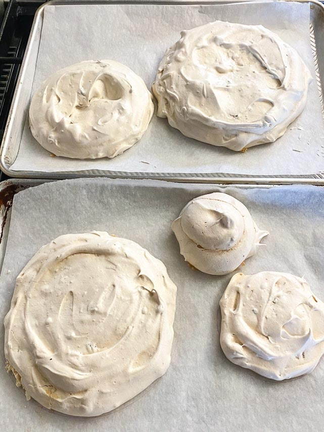 towering low FODMAP pavlova discs on two baking sheet pans