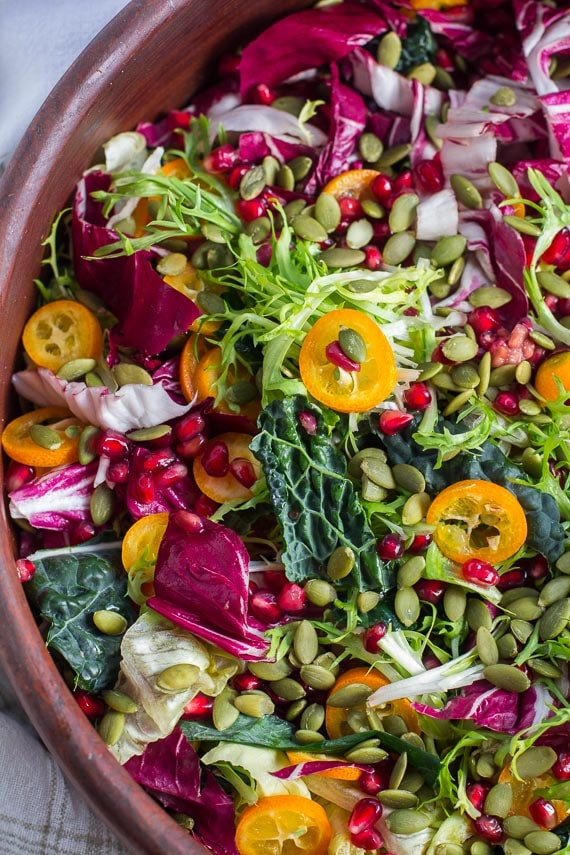 vertical closeup of Low FODMAP Greens with Kumquats and Pomegranate