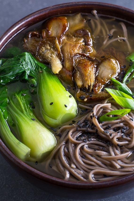 vertical image of Low FODMAP Soba Miso Soup with Bok Choy in brown ceramic bowl