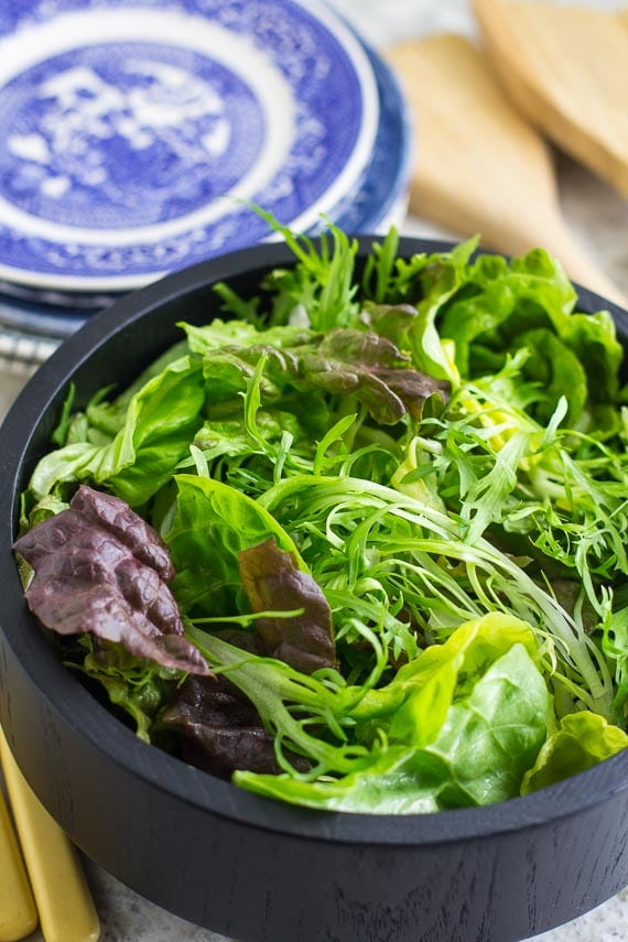 vertical of No FODMAP Leafy Green Salad closeup in wooden bowl