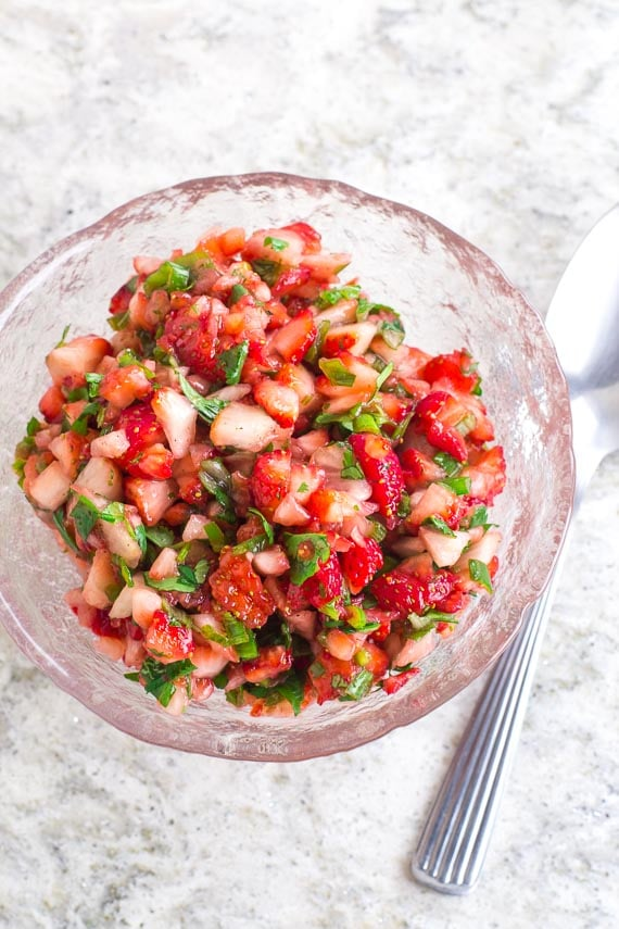 vertical strawberry salsa in glass bowl with serving spoon